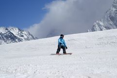 Snowboarder downhill on ski slope in high snowy mountains Stock Photos