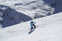Snowboarder downhill on ski slope in high snowy mountains Royalty Free Stock Images