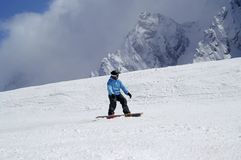 Snowboarder downhill on snowy ski slope in high mountain Royalty Free Stock Image