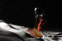 Snowboarder riding on board at night under the snow. Snowboarder dressed in orange and black sportswear riding on the board in the dark under the snow royalty free stock photos