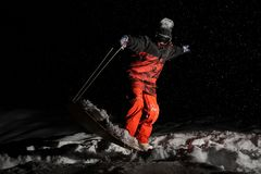 Snowboarder dressed in the orange sportswear balancing on the bo. Ard at the dark snowy night stock photo