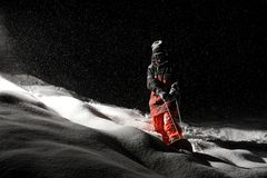 Snowboarder dressed in the orange sportswear riding on the board. At the dark snowy night stock photography