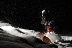 Snowboarder dressed in the orange sportswear riding with the sno. Wboard at the dark snowy night stock photography