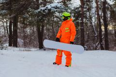 Snowboarder posing in winter forest. Snowboarder dressed in orange suit posing in winter forest royalty free stock image