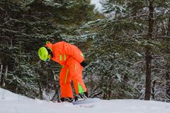Snowboarder posing in winter forest. Snowboarder dressed in orange suit posing in winter forest stock photos