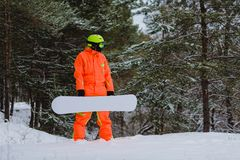 Snowboarder posing in winter forest. Snowboarder dressed in orange suit posing in winter forest royalty free stock images