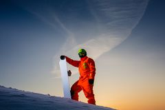 Snowboarder on the top of the ski slope at the background of beautiful sunset. Snowboarder dressed in orange suit on the top of the ski slope at the background royalty free stock image