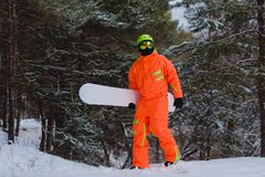 Snowboarder walking through the forest. Snowboarder dressed in orange suit walking through the forest stock images