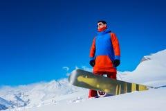 Snowboarder elegante del atleta contra la perspectiva de las montañas de la nieve Imagen de archivo libre de regalías