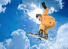 Snowboarder en el salto anaranjado de los guardapolvos Imagen de archivo libre de regalías