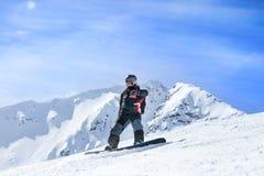 Snowboarder en la acción en las montañas Imagen de archivo libre de regalías