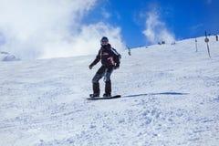 Snowboarder en la acción en las montañas Foto de archivo libre de regalías