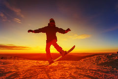 Snowboarder en la montaña con una puesta del sol Imagen de archivo