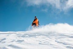 Snowboarder en la ropa de deportes anaranjada que monta abajo de la colina de la nieve del polvo Fotografía de archivo