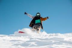 Snowboarder en la ropa de deportes elegante que monta abajo de la colina de la nieve del polvo Imagen de archivo
