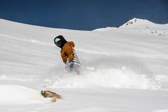 Snowboarder en la ropa de deportes que monta abajo de la cuesta de montaña Fotografía de archivo