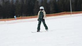 Snowboarder en las precipitaciones de la velocidad de las montañas nevadas al centro turístico ucraniano metrajes