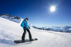 Snowboarder en piste en altas montañas Fotos de archivo libres de regalías