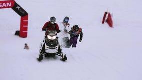 Snowboarder en skiërrit op sneeuwscooterholding op kabel Het van brandstof voorzien van de benzinepomp sneeuw stock footage