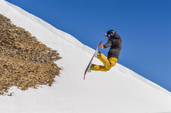Snowboarder enjoying runs and jumps on spring`s last snow. Stock Photos
