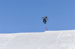 Snowboarder enjoying runs and jumps on spring`s last snow. Stock Images