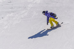 Snowboarder enjoying runs and jumps on spring`s last snow. Royalty Free Stock Photo