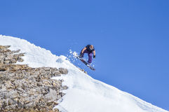 Snowboarder enjoying runs and jumps on spring`s last snow. Royalty Free Stock Image