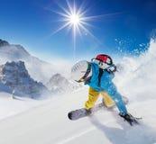Snowboarder för ung man som kör ner lutningen i alpina berg Arkivbild