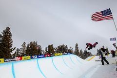 Snowboarder flies out of the half-pipe during a competition, Mammoth Mountain, California USA. Professional skiers and snowboarders are watched by an impressed Stock Image