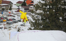 Snowboarder flying over Arena Platos, Paltinis. Arena Platos, Paltinis, near Sibiu, Romania - 2 February 2013: Arena Freestyle Open - Ski and Snowboard Royalty Free Stock Photos