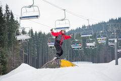 Snowboarder flying over a hurdle in winter day. Snowboarder slides down over a hurdle in winter day with snow-covered firs and ski lifts in background at a Stock Photos