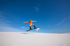 Snowboarder is flying over the sand dune. Stock Photo