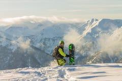 Snowboarder freerider стоит в снежных горах в зиме под облаками Стоковое Изображение