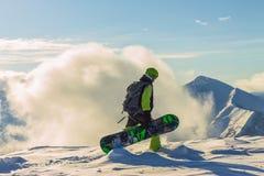 Snowboarder freerider стоит в снежных горах в зиме под облаками Стоковая Фотография