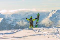 Snowboarder freerider стоит в снежных горах в зиме под облаками Стоковое фото RF