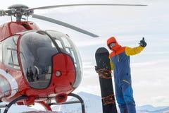 Snowboarder freerider стоит на вертолете в снежных горах в зиме под облаками Стоковая Фотография RF