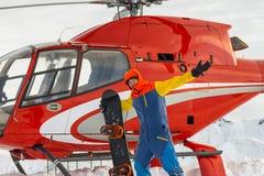 Snowboarder freerider стоит на вертолете в снежных горах в зиме под облаками Стоковое Изображение RF
