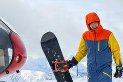 Snowboarder freerider стоит на вертолете в снежных горах в зиме под облаками Стоковое фото RF