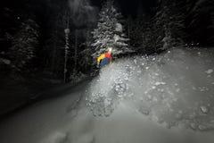 Snowboarder Freerider che salta alla notte con un trampolino nella foresta immagini stock