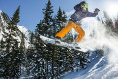 Snowboarder freerider jumping from a snow ramp in the sun on a background of forest and mountains Stock Photos