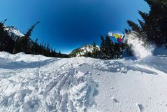 Snowboarder freerider jumping from snow ramp. Wide-angle aerial panorama Royalty Free Stock Photography