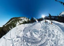 Snowboarder freerider jumping from snow ramp. Wide-angle aerial panorama Stock Image