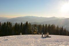 Snowboarder gestoppt, um ein Foto auf einem Hintergrund von den Fichten zu machen bedeckt mit Schnee in den Bergen Karpaten Stockbilder