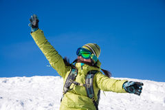 Snowboarder girl. Young woman on a snowy slope with raised hands royalty free stock images