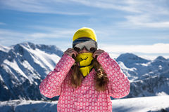 Snowboarder girl against the mountains. Portrait of young woman standing on a background of rocks royalty free stock photos