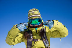 Snowboarder girl in bright clothes. Young woman against the blue sky is showing fingers on the mask stock photography