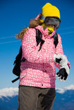 Snowboarder girl dressing gloves. Young woman is standing on the peak and correcting her clothes stock photo