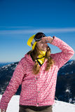 Snowboarder girl looking up. Portrait of young woman standing on the mountain and watching over the sky stock image