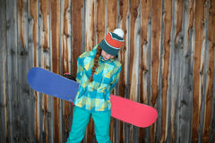 Snowboarder girl resting on the terrace of a wooden house Stock Photo