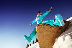 Snowboarder girl sits on the stone  blue sky backdrop Royalty Free Stock Photos